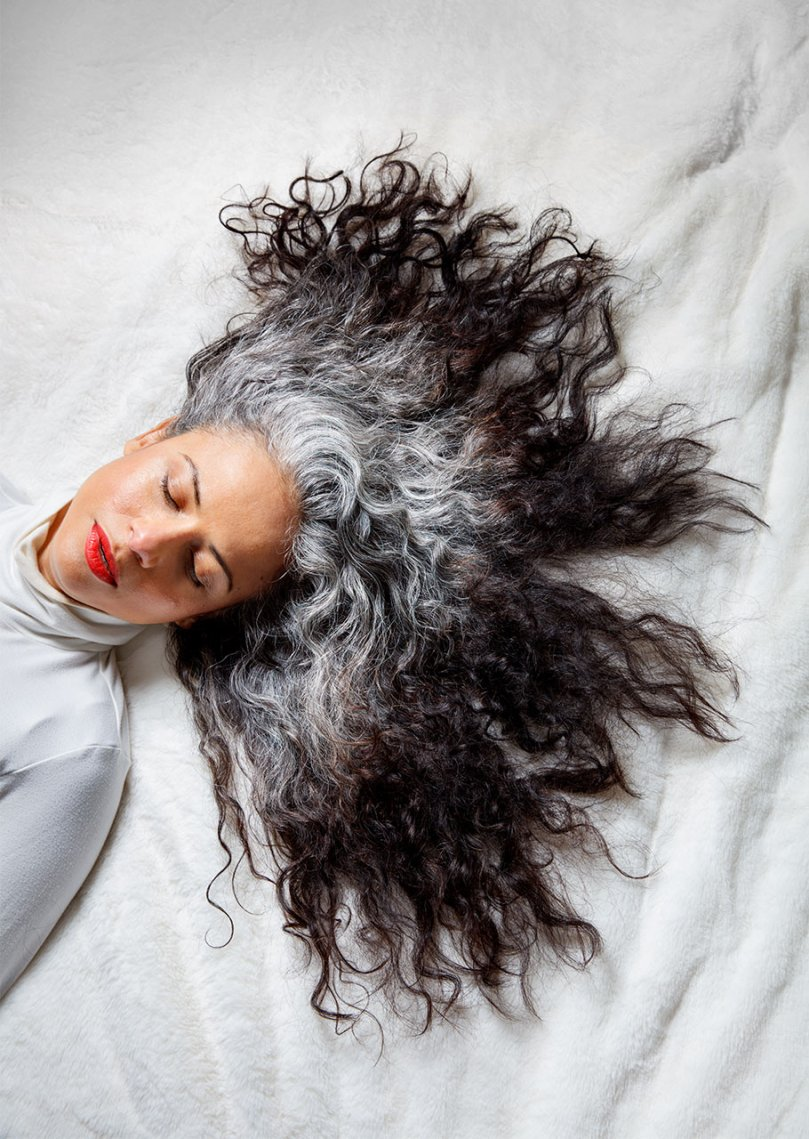 Woman with silver curly hair and dyed ends splayed out.