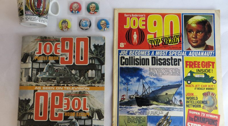 A Joe 90 Comic Number One, published in 1969, with Joe 90 puzzle book, Washington pottery mug and badges, being offered at auction in Cardiff today by Langley and Jones