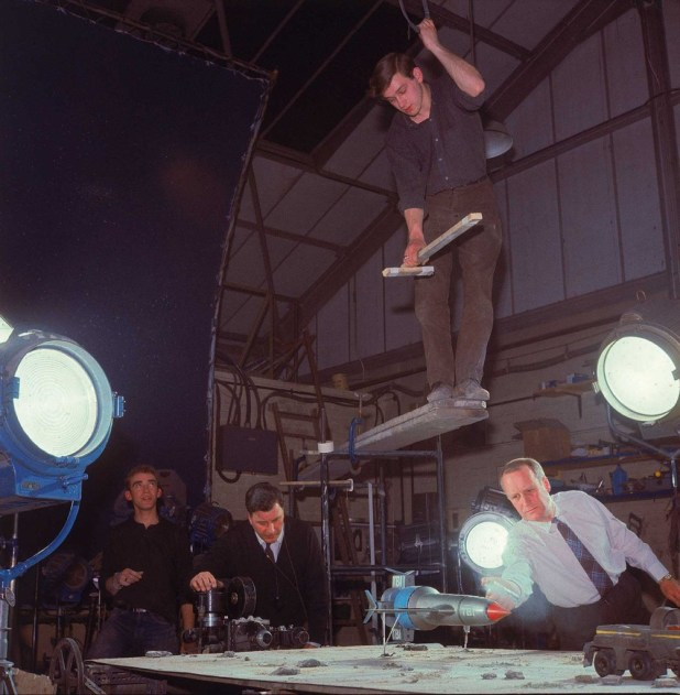 Special effects floor technician (far left) and special effects second unit lighting cameraman Harry Oakes (centre) preppare a scene for the episode Martian Invasion. Floor technician Peter Wragg balances on planks overhanging the set, ready to fly Thunderbird 1.