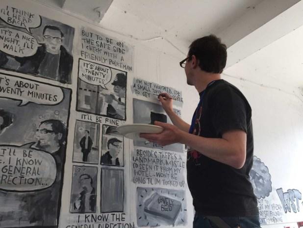 Comic artist Joe Decie at work on a mural near Ruskins Bar during the weekend. Photo: John Freeman