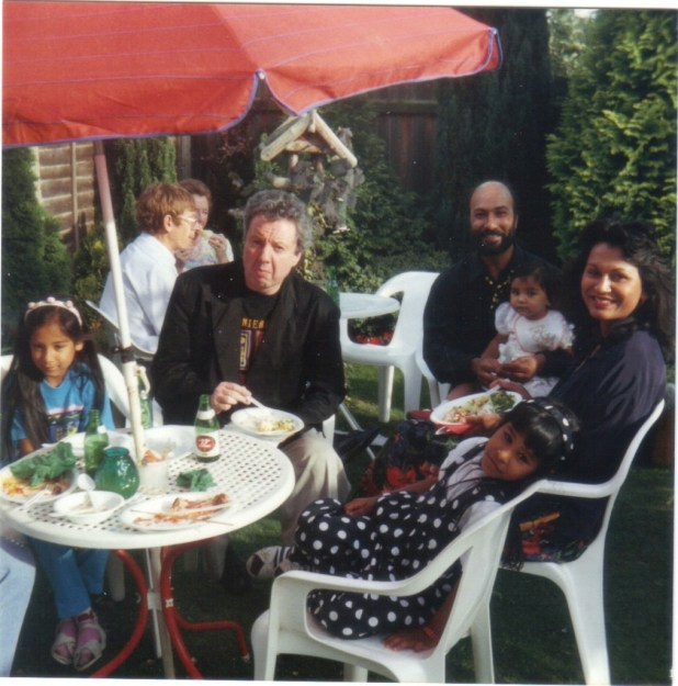 Gerry Dolan (seated at table) with Helicopter studios artist Satnum Kundi and his family in the 1980s. Photo courtesy Marise Morland-Chapman