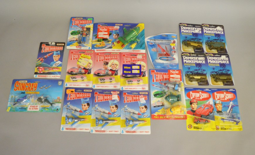 18 carded diecast TV related models including thirteen Matchbox Gerry Anderson related items - 10 x Matchbox Thunderbirds and 1 x Matchbox Stingray together with two Vivid Imaginations 'Captain Scarlet' models, additionally there are four from the Rainbow Toys 'Dempsey and Makepeace' range and an FEVA Thunderbird 3 carded model.