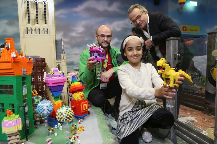 "James Windle, Richard Watson and Saira Ali beside her LEGO-realised winning entry in a nationwide ""Cities of the Future"" competition at LEGOLAND Discovery Centre Manchester"