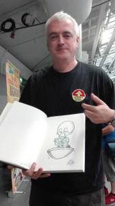Longtime Dan Dare Simon Belmont, with a Mekon cartoon drawn by Lew Stringer. Photo: Lew Stringer