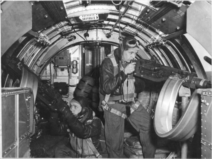 "Boeing B-17F-30-BO Flying Fortress ""Invasion 2nd"" (42-5070) of the 8th Air Force, 91st Bombardment Group, 401st Bombardment Squadron. In the waist gunner positions are Staff Sergeant Eldon R. Lapp of Fort Wayne, Indiana and Staff Sergeant William D. King operating the Browning .50 caliber (12.7 mm) machine guns for a Signal Corps photographer"