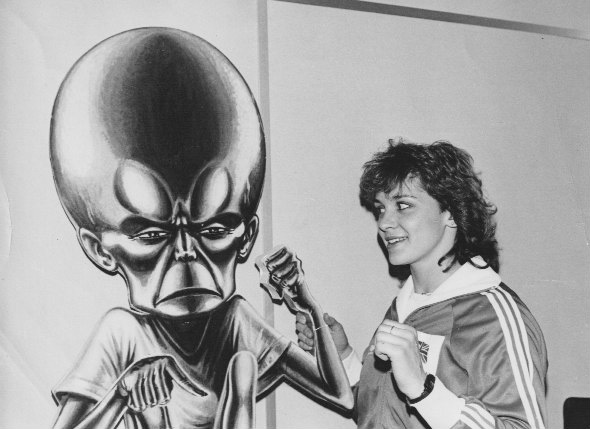 """Kathy Tayler, champion modern pentathlete, now a TV presenter drops into the Roy of the Rovers office and encounters  the dreaded Mekon, who had escaped from  Eagle. """"The Mekon's hand had broken off and Kathy is kindly holding it in place!"""" Barrie recalls. Image via Barrie Tomlinson"""