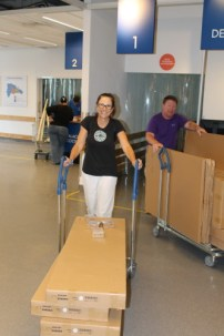 Mary and Greg rolling the Ikea carts with the tables and the cabinets