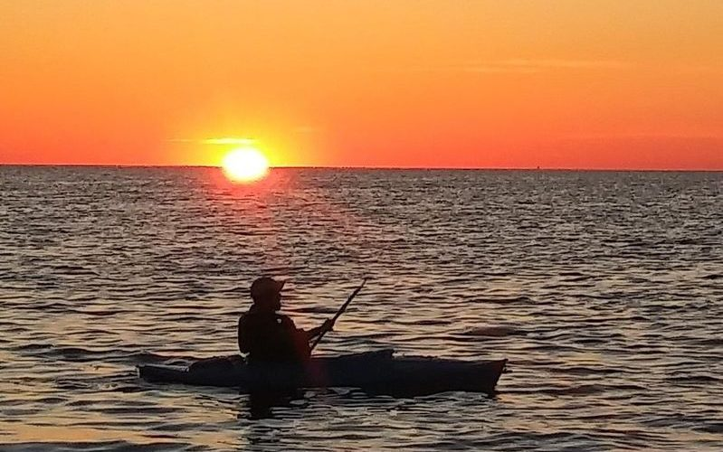Sillouhette of a kayaker in foreground with sunset and orange sky in background.