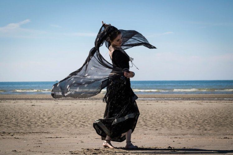 A woman dressed in black flowing gown walking along a beach.