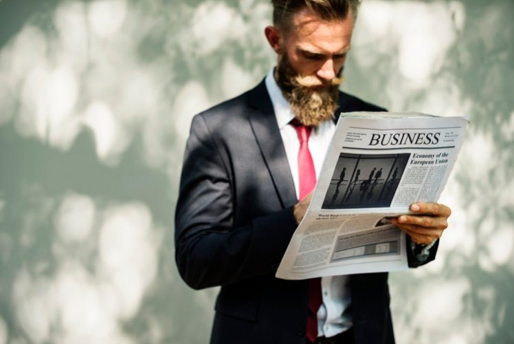 A corporate boss reading the business news.