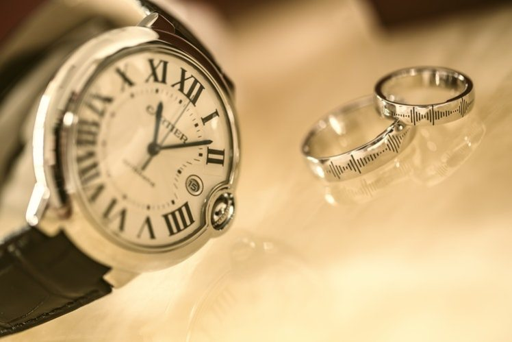 A picture of a watch and wedding rings.