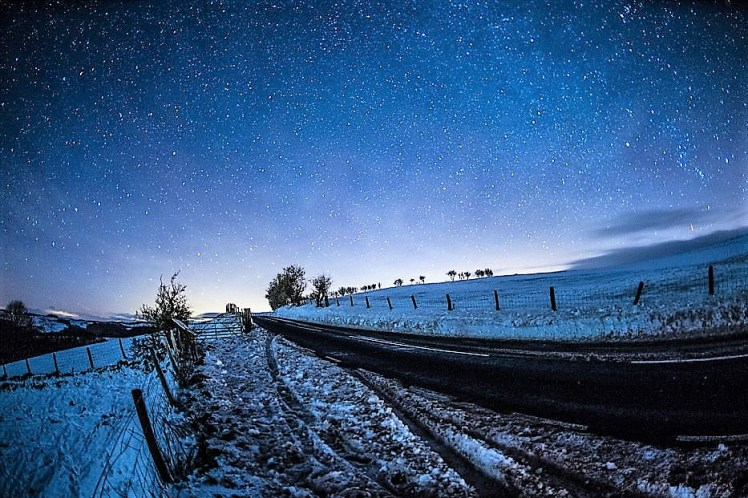 A blue hue falls over the snow filled fields.