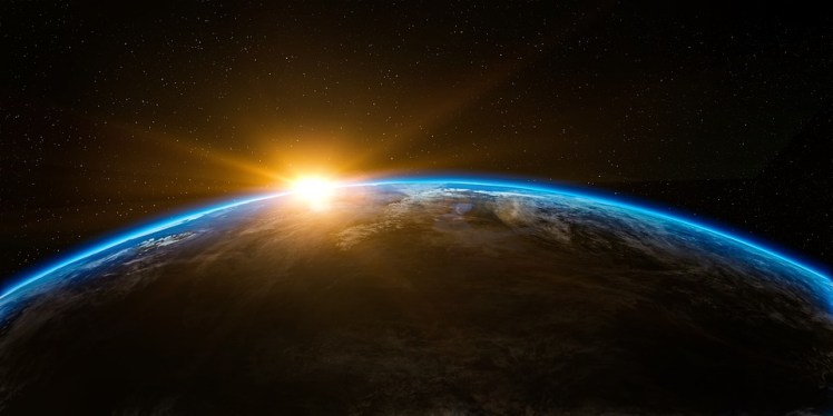 The sun peaks through the Earth's atmosphere.