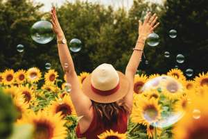 Girl standing in a field of sunflowers with her hands raised to the sky.