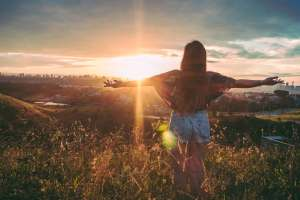 Girl standing in a field with her arms wide open gazing off at a sunset.