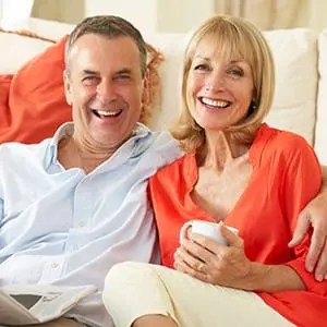 Benefits strategies for Baby Boomers; Caucasian middle aged couple sitting in front of a couch and smiling