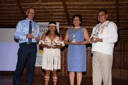Minister of Indigenous Peoples' Affairs, Sydney Allicock and Minister within the Ministry, Valerie Garrido-Lowe, Minister of Business, Dominic Gaskin and a young Makushi girl who is the face of the Rupununi Essence brand pose for a photo opportunity at the launch.