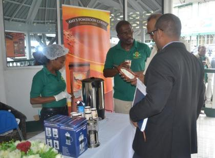 A member of Amy's Pomeroon Foods Inc explaining the details of their coffee to customers .JPG-june16