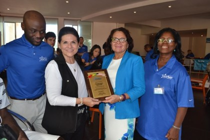 First Lady, Mrs. Sandra Granger (second from right) and Mrs. Tani Austin (second from left), Co-Founder, Starkey Hearing Foundation display a plaque celebrating their partnership to augment hearing health care in Guyana and the Caribbean. Dr. Luqman Lawal (first, left) and Dr. Ruth Quaicoe (first, right) are also pictured.