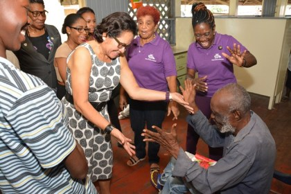 Mr. Lewis  Hart, a resident of The Palms Geriatric Home charms First Lady, Mrs. Sandra Granger  when she visited the facility to host a special 'spa' exercise for the male residents.