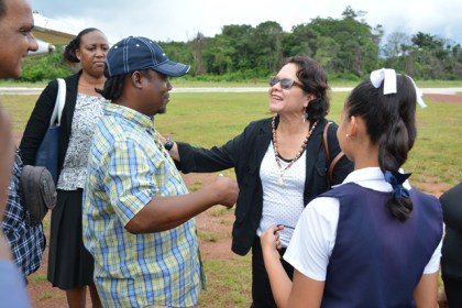 First Lady, Mrs. Sandra Granger greets Mahdia businessman Mr. Roger Hinds as student, Ms. Lucianna Thomas waits to drape a beaded flag-colour necklace around her neck. Mr. Hinds explained that the necklace is a handmade gift from 65-year-old Ms. Marlyn Gouveia.