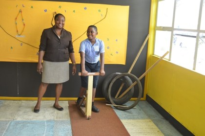 Administrator of the Guyana National Museum, Tamika Boatswain shares in a child's enjoyment of a wooden scooter