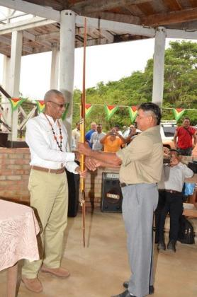 """President David Granger receiving an arrow and bow, which he called a """"silent missile"""" from Daniel Allicock of Surama Village"""