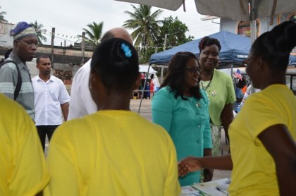 Minister in the Ministry of Public Health, Dr Karen Cummings interacting with persons at one of the booths at the health fair