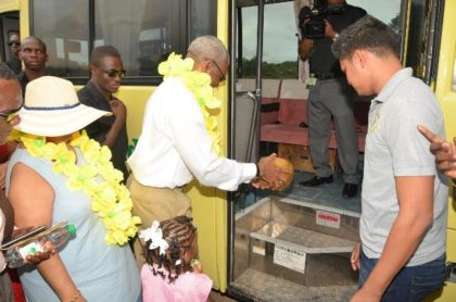 President David Granger pours coconut water to officially commission the 30-seater bus, while Minister of Social Cohesion, Ms. Amna Ally looks on. Sajid Baksh, a representative of the donor, Mr. Suresh Jagmohan is at right.