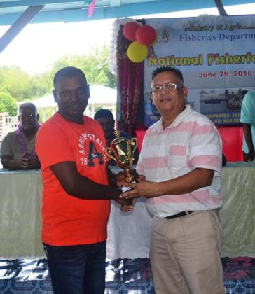 Head of the Ministry of Agriculture's Fisheries Dept. Mr Denzil Roberts handing over a trophy to one of the participants in the Fisherfolk Day celebrations