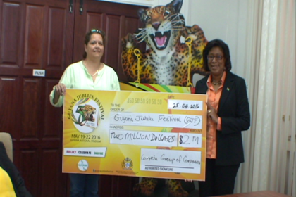 Minister of Public Telecommunications Catherine Hughes receives cheque from Nicole Correia, Chief Finance Officer, Correia Group of Companies