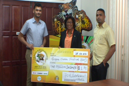 Minister of Public Telecommunications Catherine Hughes receives cheque from 704 Sports Bar representatives