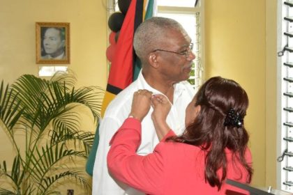 Minister within the Ministry of Communities, Ms. Dawn Hastings-Williams pins a special pin on President Granger, as a token of appreciation from the People's National Congress.