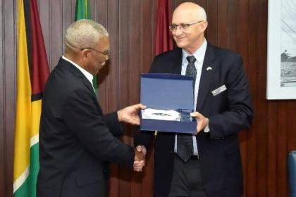 President Granger receives a token of appreciation from Colonel (Retired) Gus Greene, Director, Industrial Security Field Operations, Defense Security Service, United States of America.