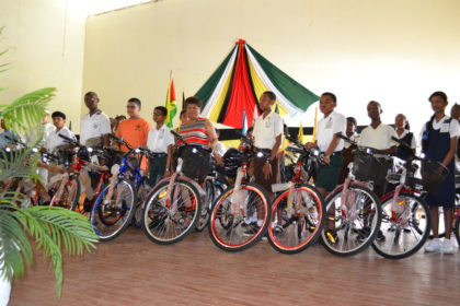 Minister of Social Cohesion, Ms. Amna Ally and some of the Demerara-Mahaica recipients of bicycles and backpacks, this morning, in the Queen's College auditorium