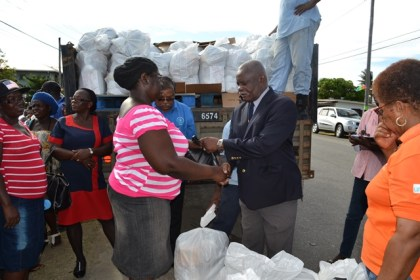 Minister of Citizenship, Mr. Winston Felix presents a parcel to one recipient at the Community Development Centre at Union Village, even as CDC Chairman Colonel (ret'd) Chabilall Ramsarup (blue shirt) makes a final check of the list of beneficiaries.