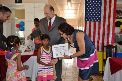 First Lady Mrs. Sandra Granger hands over a certificate to one of the youngest graduates.