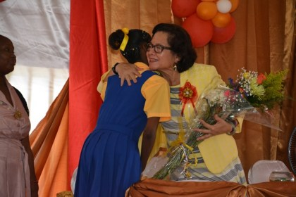 First Lady, Mrs. Sandra Granger shares a warm embrace with Best Graduating Student Ms. Jada Leitch, after she presented her with a bouquet in appreciation for her attendance at the graduation ceremony.