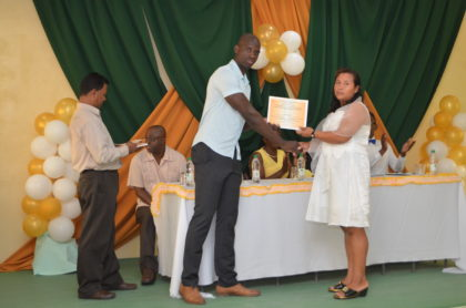 Mr. Ronald Austin of the Office of the Presidential Advisor on Youth Empowerment presents a certificate to Ulita Henry