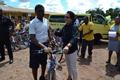 The First Lady smiles as this lad does his best to maintain his composure after having been presented with a bicycle.