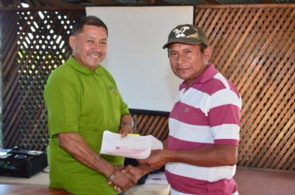 Minister of Indigenous Peoples' Affairs, Sydney Allicock handing over a cheque to a toshao of one of the beneficiary villages