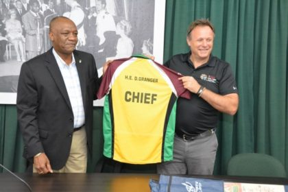 Chief Operations Officer of the Caribbean Premier League Franchise, Mr. Pete Russell presents the 'Chief' Amazon Warriors t-shirt for President David Granger to Minister of State, Mr. Joseph Harmon.
