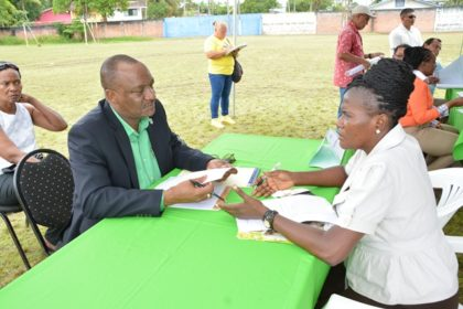Minister of State, Mr. Joseph Harmon listening to this resident explain her challenges during the Meet the Public event at the Mckenzie Sports Club Ground in Linden today.