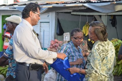 Public Security Minister, Khemraj Ramjattan distributing fliers and other items to raise awareness of trafficking in persons to members of the public around the Bourda Market area.