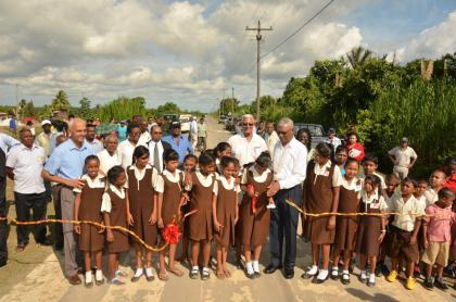 Students of the Parika Primary school help the President to cut the ceremonial ribbon for the opening of the Parika Paved Road, which is 8.2 km long