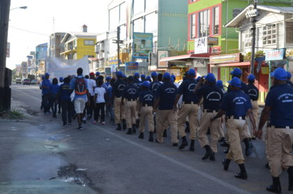 Members of the Community Policing Groups taking part in the Ministry of Public Security's Awareness Walk to commemorate World Day Against Trafficking in Persons
