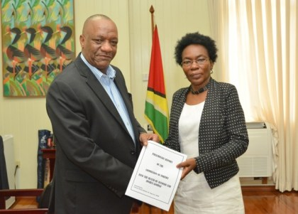 Minister of State, Mr. Joseph Harmon receiving the Preliminary Report of the Commission of Inquiry into the Hadfield Street Drop In Centre fire from Commissioner, Retired Colonel Windee Algernon.