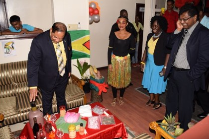 Prime Minister Moses Nagamootoo examines the Guyana exhibit at the CARICOM Culture Day activity at the Ministry of Public Security. Public Security Minister Khemraj Ramjattan looks on.