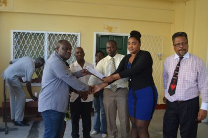 The report being handed over by labour officers Roydon Croal (centre) and Latoya John (Right) to Town Clerk Royston King (left) accompanied by Chief Labour Officer Charles Ogle