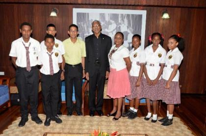 President David Granger is flanked by Ms. Carol Monroe (right) and Mr. Bruce Monroe (left) and students of the Phoenix Elementary School,  during their visit to the Ministry of the Presidency earlier today.